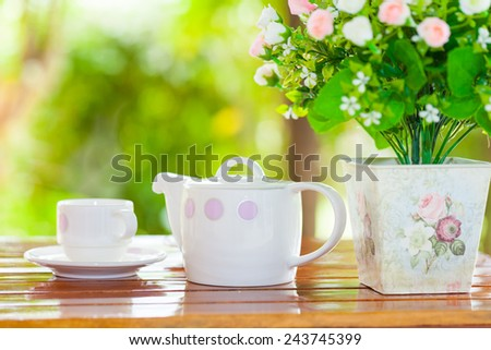 White porcelain set for tea or coffee on wooden table in the garden over blur green nature background, shallow DOF teapot in focus - stock photo
