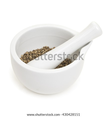 White porcelain set mortar and pestle with coriander grains. Isolated on white. - stock photo