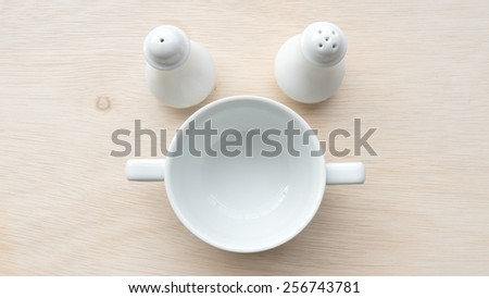 White porcelain soup, salt and pepper tableware container on wooden surface. Shot with natural light. Concept of clean and simplicity kitchen table. Slightly defocused and close-up shot. Copy space. - stock photo