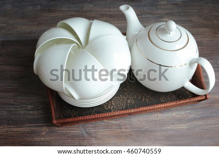 White porcelain tea set on a wooden tray. Stacked cups and saucers and tea pot. Special light.