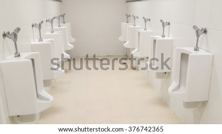 white porcelain urinals in public toilets - stock photo