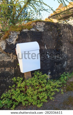 White post box over rock background
