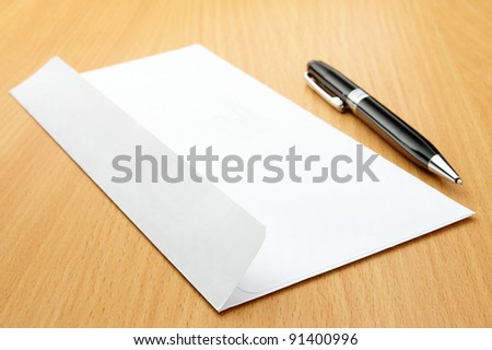 White post envelope and black ball pen on a wooden table