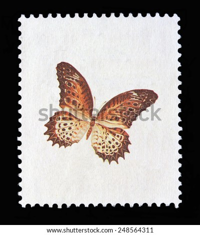White postage stamp on black background with the picture of a butterfly. The butterfly pic is in the center and is quite big (about 1/2 of stamp surface. - stock photo