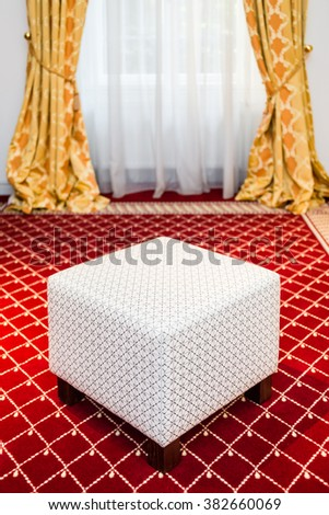 White pouf in the room with vintage red carpet and classic yellow drapes - stock photo