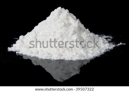 White powder on black reflective surface, closeup - stock photo