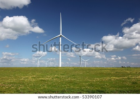 White power generating wind turbines, windmills against  blue sky, yellow wildflowers, on agricultural green pastures - stock photo