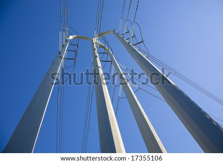 White power pole tower with lots of power lines from its base to the blue sky