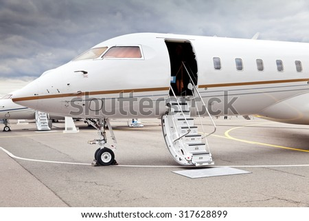 White private business jet and open ladder at the airport - stock photo