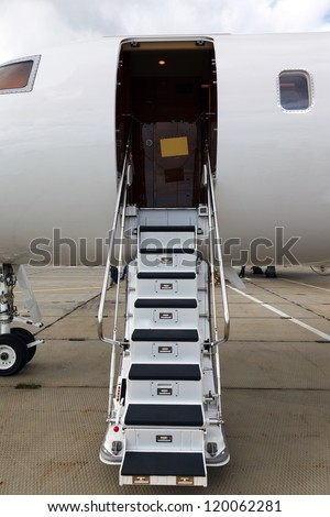 white private jet and open ladder at the airport on a background cloudy sky - stock photo