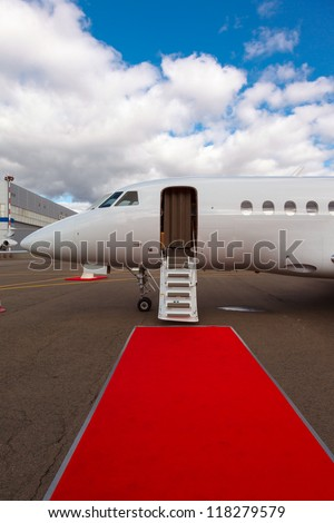 white private jet and open ladder, red carpet at airport, background blue sky - stock photo
