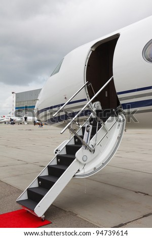 white private jet and open ladder, red carpet at airport on background cloudy sky