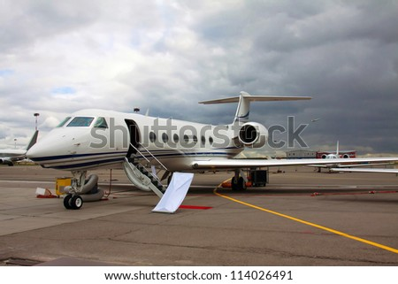 white private jet and open ladder, red carpet at the airport on a background cloudy sky - stock photo