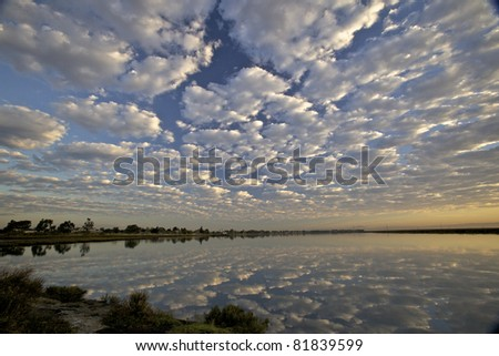 white puffy clouds over calm  bay and reflection of clouds on the water and blue sky - stock photo