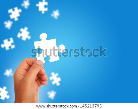 White puzzle in hand over white background.