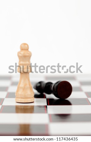 White queen standing with black queen lying at the chessboard - stock photo