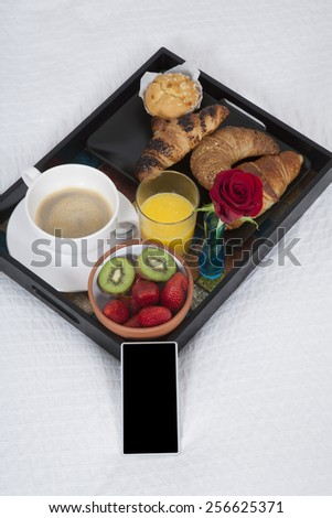 white quilt bed breakfast black tray croissants orange juice strawberry kiwi cupcake red rose flower and smartphone blank screen - stock photo