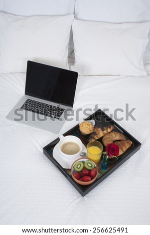 white quilt bed breakfast black tray croissants orange juice strawberry kiwi cupcake red rose flower and silver laptop blank screen - stock photo
