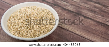 White quinoa grain in white bowl over wooden background - stock photo