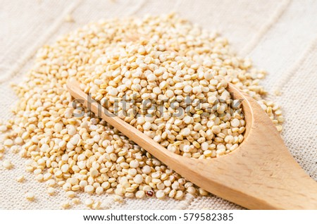 White quinoa seeds in wooden scoop on fabric background.