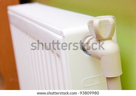 White radiator with radiator thermostat at home. - stock photo