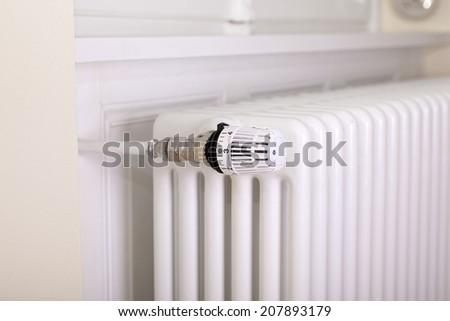 White radiator with white thermostat - stock photo