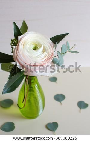white ranunculus  in green glass vase near the window - stock photo