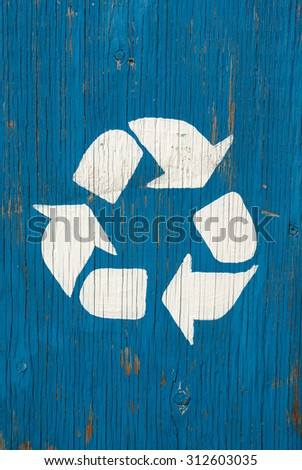 white recycling logo sign on blue  rustic old cracked wood panel - stock photo