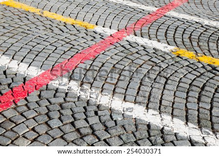 White, red and yellow road marking lines over on gray cobblestone pavement, abstract urban background - stock photo