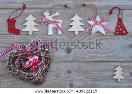 White red christmas decoration as christmas tree, reindeer and star on a old grey wooden planks background with empty copy space