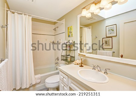 White refreshing bathroom with tile wall trim and white curtains. White bathroom cabinet with beautiful sink and large mirror - stock photo