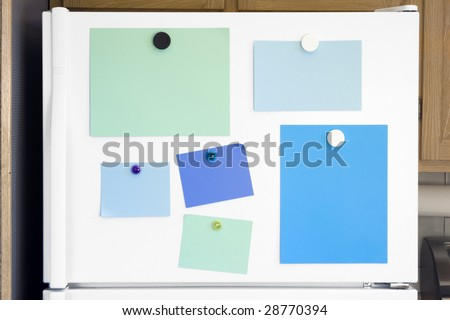White refrigerator door with colorful notes for lists and messages, posted with magnets. - stock photo