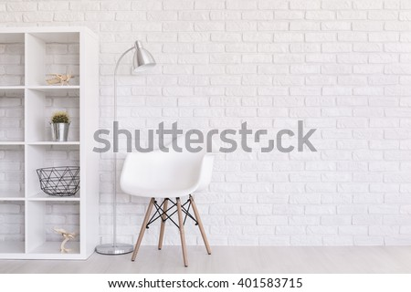 White regale with home decorations, standing lamp and modern chair standing in light room with brick wall design - stock photo
