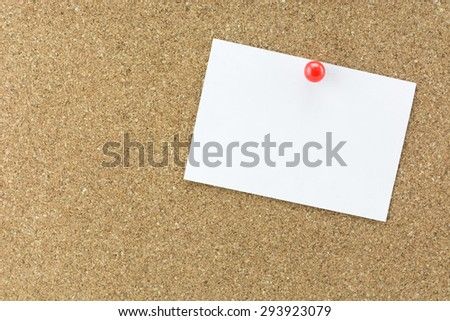 White reminder sticky note on cork board, empty space for text
