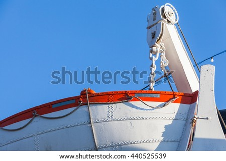 White rescue boat on a passenger ferry above blue sky background - stock photo