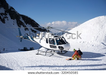 White rescue helicopter parked in the snowy mountains - stock photo