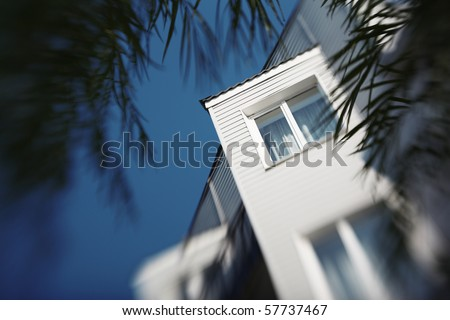White residential building detail over blue sky. Selective focus, shallow DOF. - stock photo