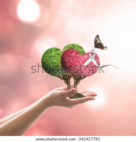 White ribbon awareness on red/ green heart tree with butterfly on woman's hand on blur abstract orange autumn color background: International Day for the Elimination of Violence against Women concept  - stock photo