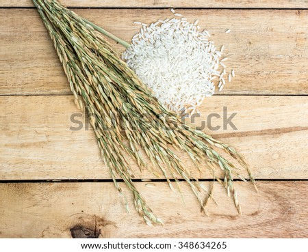white rice and paddy pile on wood background