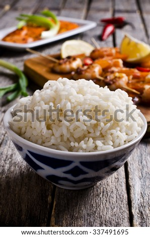 White rice cooked on a background of shrimp on skewers and salad with carrots. Selective focus. - stock photo