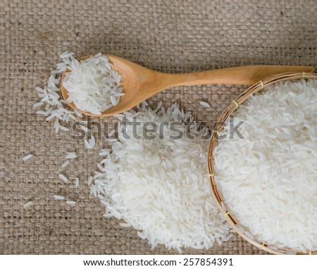 white rice grains with wooden spoon  on sackcloth - stock photo
