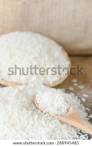 white rice  grains with wooden spoon on wooden table