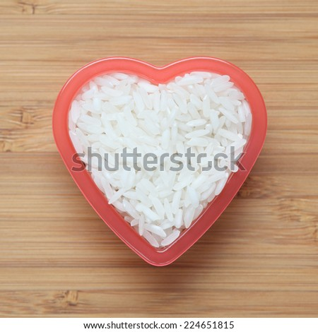 White rice heap in a heart bowl. Close-up. - stock photo