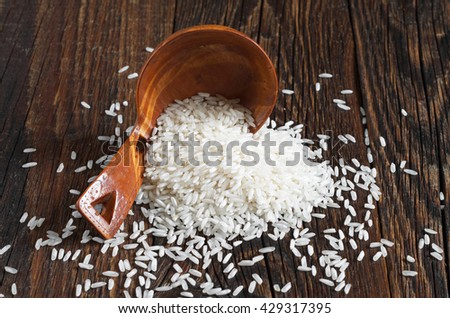 White rice in a spoon and an old wooden table - stock photo