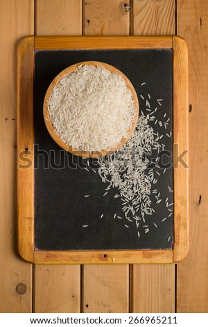 White rice in a wooden bowl on a small chalkboard - stock photo