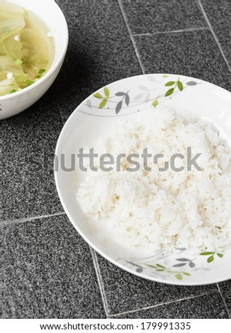 white rice in dish with lettuce soup thai style food on grey tile at outdoor sunshade