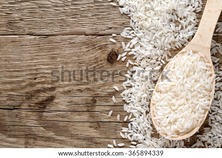 White rice in spoon on wooden table top view - stock photo