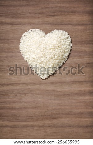 white rice in the shape of a heart over a wooden background - stock photo