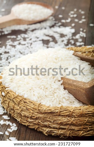 White rice in wicker bowl with wooden spoon on wooden table