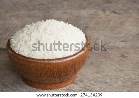 White rice in wood cup have wood table is background.